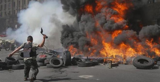 Un activista del Maidán lanza un cóctel molotov durante una protesta contra las autoridades ucranianas que tratan de limpiar la calle.