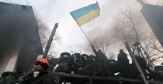 Un manifestante proeuropeo ondea una bandera ucraniana sobre una barricada en la PLaza de la Independencia de Kiev.