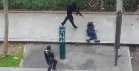 Imagen de un video amateur en el que se ve a uno de los atacantes de la revista 'Charlie Hebdo' disparando contra un policía que yace herido en el suelo. REUTERS