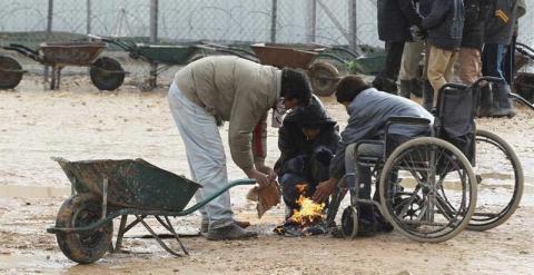 Refugiados sirios se calientan con una pequeña hoguera en el campo de refugiados Zaatari, cerca de Mafraq, Jordania. /EFE