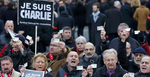 French journalists holding up their Press card take part in a hundreds of thousands of French citizens solidarity march (Marche Republicaine) in the streets of Paris January 11, 2015. French citizens will be joined by dozens of foreign leaders, among them