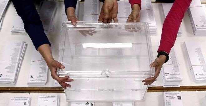Tres personas sujetan una urna sobre las papeletas en un colegio electoral. EFE