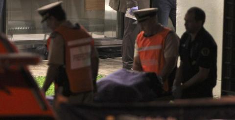 Agentes de policía trasladan el cuerpo sin vida del fiscal argentino Alberto Nisman. EFE/David Fernández