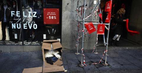 Una mujer sale de una tienda en rebajas mientras un hombre duerme en unas cajas en la calle en Madrid. REUTERS