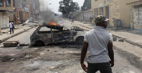 Un hombre junto a un coche quemado en Kinshasa a modo de barricada. - REUTERS