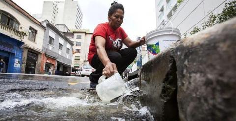 Una mujer se surte de agua debido a que su negocio sufre cortes de suministro. - EFE