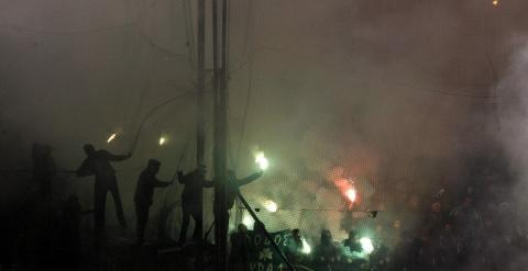 Aficionados del Panathinaikos lanzan bengalas durante el derbi. REUTERS/Kostas Tsironis