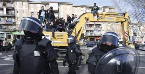 Agentes de Policía Municipal ante las personas subidas en una excavadora que trataban de evitar el desalojo de la vivienda en el número 29 de la calle Ofelia Nieto./ EFE-Javier Lizón