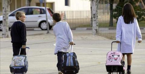 Dos niños y una niña, camino del colegio./ EFE
