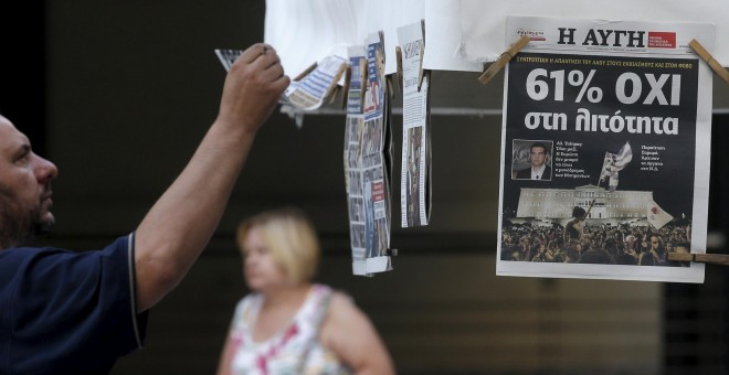 A man looks at newspapers showing the results of yesterday's referendum in central Athens, Greece, July 6, 2015. Greeks overwhelmingly rejected conditions of a rescue package from creditors on Sunday, throwing the future of the country's euro zone members