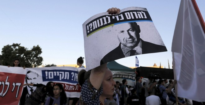 An Israeli protester holds a placard depicting Israeli Prime Minister Benjamin Netanyahu during a demonstration against a court decision to demolish housing units in the Jewish settlement of Beit El, outside the Supreme Court in Jerusalem July 8, 2015. Is