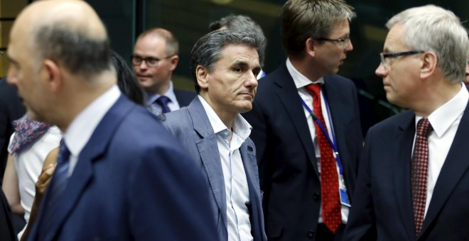 Greek Finance Minister Euclid Tsakalotos walks past Lithuanian counterpart Rimantas Sadzius (R) and European Economic and Financial Affairs Commissioner Pierre Moscovici (L) during an euro zone finance ministers meeting in Brussels, Belgium, July 11, 2015