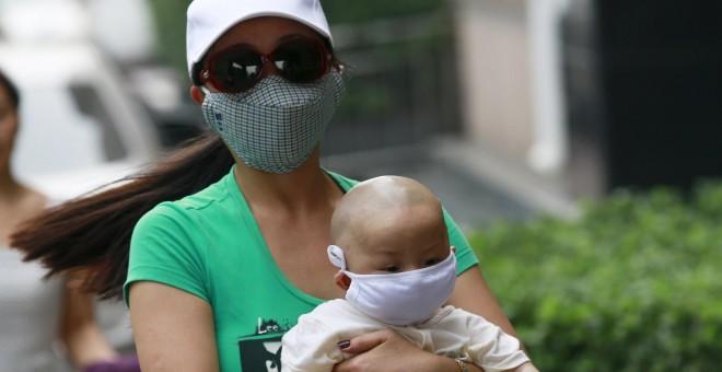 Una mujer con un bebé, ambos con máscaras, caminan por las calles de Tianjin. REUTERS