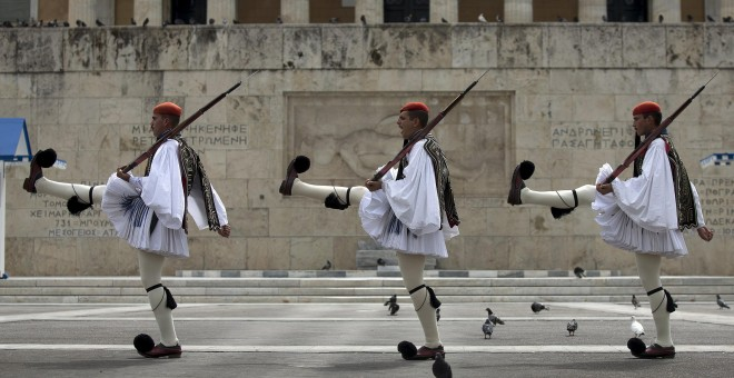 Greek Presidential guards take part in a ceremonial change of guards at the Monument of the Unknown Soldier in front of the Parliament building in Athens.- REUTERS.