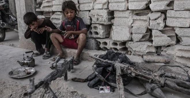 Dos niños permanecen en Kobani, Siria, junto a varias armas incautadas a combatientes del Estado Islámico. - AFP