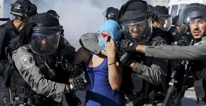Un policía israelí detienen a un manifestante palestino durante los enfrentamientos que se produjeron en el campamento de refugiados de Shuafat, cerca de Jerusalén./ REUTERS/ Ammar Awad