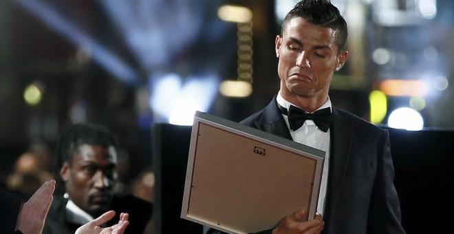 Cristiano al recibir un cuadro en la alfombra roja de la premiere de su película. /REUTERS