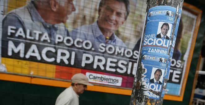 Una hombre camina frente a una valla de propaganda electoral en Buenos Aire. / EFE