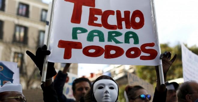 Un manifestante sujeta una pancarta donde se lee 'TECHO PARA TODOS' en la protesta convocada por la plataforma 'Nadie sin Hogar' por el derecho a la vivienda, en el centro de Madrid, España, 26 de noviembre de economía 2015. REUTERS / Paul Hanna