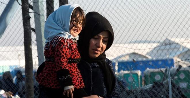 Una mujer carga a su bebé mientras se dirige al centro de registro de migrantes tras cruzar la frontera entre Macedonia y Grecua, en Macedonia. EFE