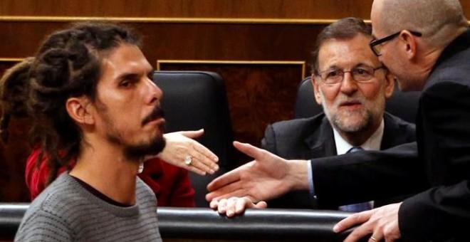 El diputado de Podemos Alberto Rodríguez (i) pasa ante el presidente del Gobierno en funciones, Mariano Rajoy, antes de votar la elección del presidente del Congreso, durante la sesión constitutiva de la Cámara Baja que supone la apertura de la XI Legisla
