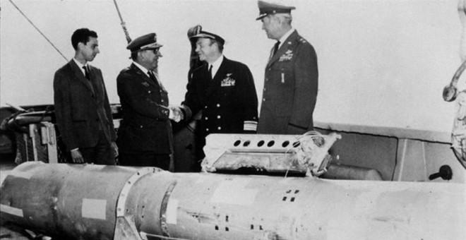 El almirante Guest estrecha la mano del general Montel junto a la cuarta bomba termonuclear rescatada del mar.