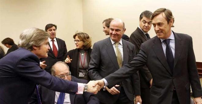 El portavoz del PP en el Congreso, Rafael  Rafael Hernando, saluda a un diputado del PP en presencia de Luis De Guindos EFE/J. J. Guillén
