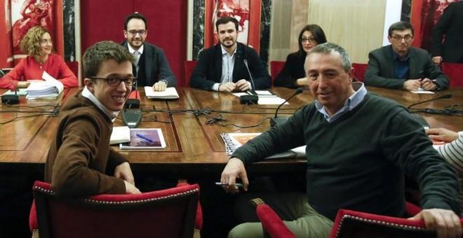 El portavoz de Pdodemos, Íñigo Errejón (i) junto a Joan Baldoví de Compromís (d) y el el portavoz parlamentario del PSOE, Antonio Hernández (2i), el líder de IU, Alberto Garzón (3i); (enfrente), entre otros, durante la reunión de los equipos negociadores