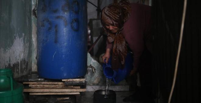 Etadal Abu Oda, una mujer palestina de 57 años de edad, toma agua de un tanque para limpiar los platos en su casa en Beit Hanoun, en el norte de la Franja de Gaza. Mohammed ABED / AFP