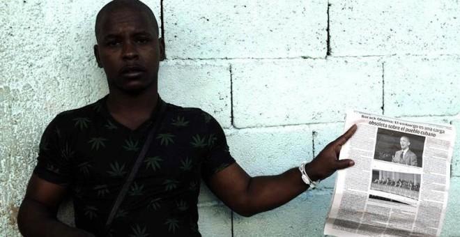 Un hombre sostiene un diario con información del presidente de EEUU, Barack Obama, en una calle de La Habana.- EFE