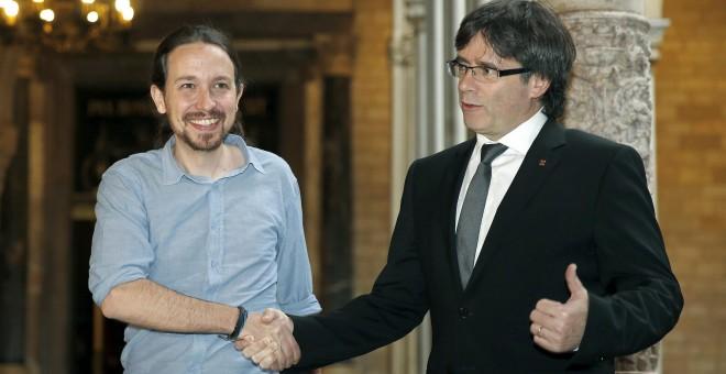 El presidente de la Generalitat, Carles Puigdemont, saluda al líder de Podemos, Pablo Iglesias, con quien se ha reunido esta tarde en el Palau. EFE/Andreu Dalmau.