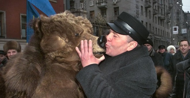 El líder del partido ultranacionalista ruso Liberal-Democrático Vladimir Zhirinovsky besa a un ruso vestido de oso durante una manifestación por el Día de la Constitución de Rusia en Moscú en 1999.- ALEXANDER NEMENOV / AFP