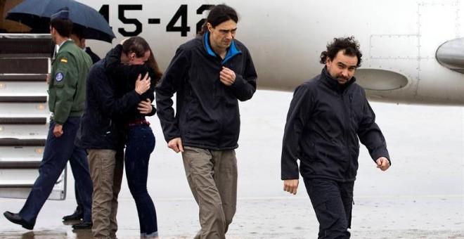 Ángel Sastre, José Manuel López y Antonio Pampliega (abrazando a un familiar) a su llegada a la Base äerea de Torrejón de Ardoz, en Madrid. - EFE