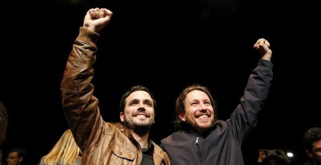 Los líderes de Podemos, Pablo Iglesias, y de Izquierda Unida, Alberto Garzón, salen de la sala Mirador, donde celebran un encuentro ciudadano, para atender a los medios tras el preacuerdo electoral alcanzado por ambas formaciones para presentarse a los c