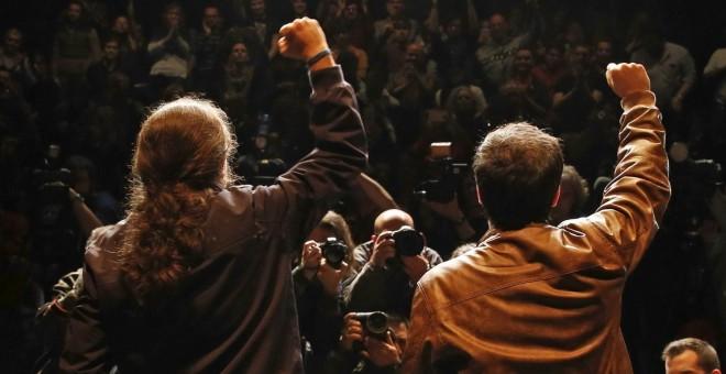 Los líderes de Podemos, Pablo Iglesias, y de Izquierda Unida, Alberto Garzón, saludan a sus seguidores y simpatizantes tras anunciar el preacuerdo alcanzado por ambas formaciones para presentarse a los comicios del 26 de junio. EFE/Ballesteros