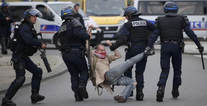 La Policía detiene a un joven durante las protestas contra la reforma laboral.- REUTERS