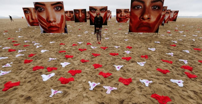 Un activista posa para la fotografía, entre ropa interior de mujeres y fotografías de Marcio Freitas durante una protesta de la ONG  Rio de Paz (Rio of Peace) contra la violencia y violación de mujeres, en la playa de Copacabana en Rio de Janeiro, Brasil.