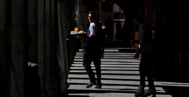 Un camarero con su bandeja en los soportales de la Plaza Mayor de Madrid. REUTERS/Sergio Perez