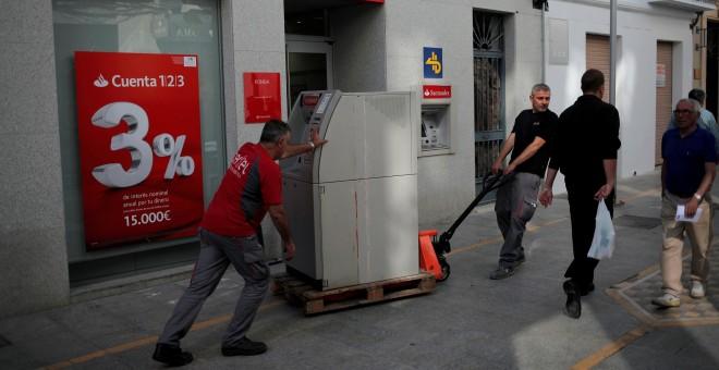 Dos operarios trasladan un cajero automático en una calle de la localidad malagueña de Ronda. REUTERS/Jon Nazca