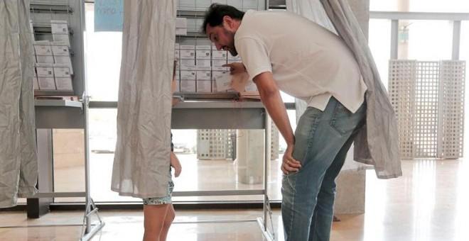 Un hombre muestra a su hijo las papeletas de los diferentes partidos en la cabina de un colegio electoral en Valencia/EFE