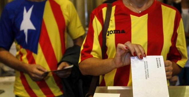 Una ciudadana deposita su voto en una mesa de en un colegio electoral de Barcelona durante el referéndum que tuvo lugar el 9-N del año 2014.- EFE