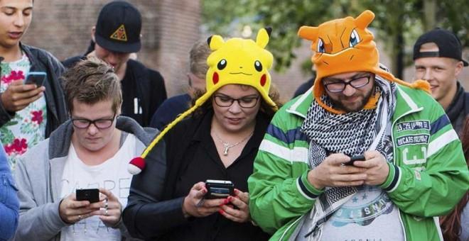 """Un grupo de personas mientras juegan al videojuego """"Pokémon Go"""" con sus móviles, en Leerdam, Holanda. EFE/Piroschka Van De Wouw"""
