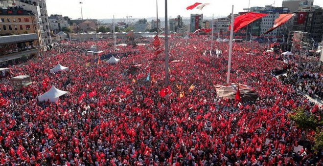 Una marea de banderas rojas cubría hoy la céntrica plaza de Taksim en Estambul, con decenas de miles de personas condenando el fallido golpe militar del 15 de julio, pero también pronunciándose contra la deriva de Erdogan.- EFE