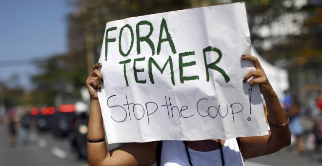 Un manifestante sujeta una pancarta en contra de Temer durante el recorrido de la antorcha olímpica en la playa de Copacabana en Río de Janeiro, Brasil. REUTERS/Benoit Tessier