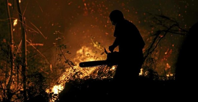 Un vecino intenta sofocar las llamas del incendio forestal de Arbo (Pontevedra), en el que se ha decretado la Situación 2 por la cercanía del fuego a núcleos de población. Las hectáreas de monte afectadas por los incendios forestales que se mantienen act