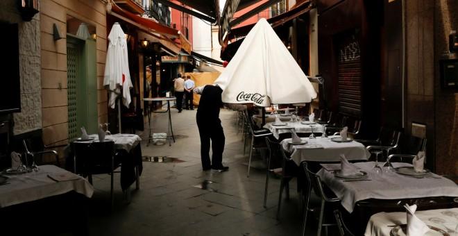 Un camarero abre una sombrilla en una terraza de un bar en Sevilla. REUTERS