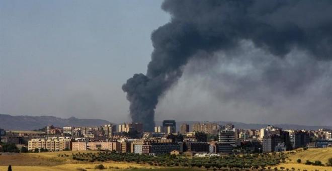 Una gran columna de humo aparece sobre el municipio de Chiloeches, Guadalajara, como consecuencia del incendio declarado esta madrugada en una planta de reciclado del polígono industrial. EFE/Pepe Zamora
