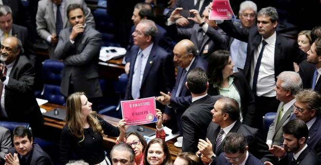 """Varios senadores sujetan carteles contrarios al """"golpe"""" contra Rousseff durante la votación en la Cámara. - REUTERS"""
