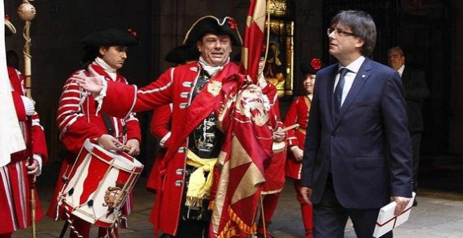 El presidente de la Generalitat, Carles Puigdemont (d), recibe a una representación de los Miquelets de Cataluña y de la Associació de Recreació Històrica La Coronela en el Palau de la Generalitat. /EFE
