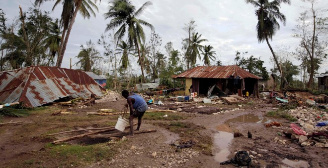 Un hombre recoge agua de una zona destrozada por el huracán Matthew, en Cavaillon, Haití. - REUTERS